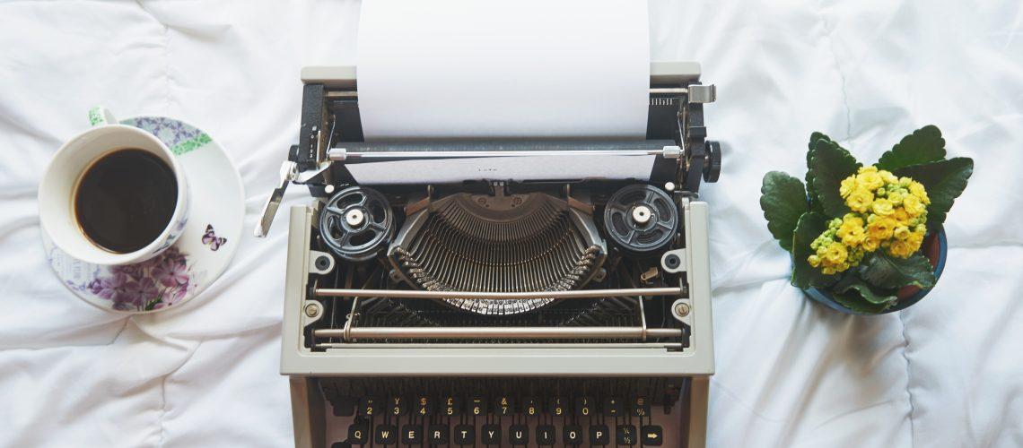 Vintage typewriter on  the bed, top view